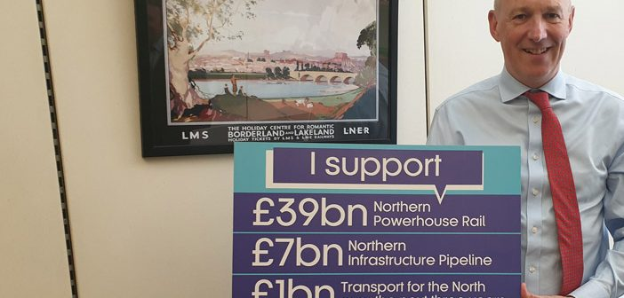 John Stevenson MP stands with sign declaring support for Transport for the North funding